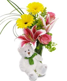 Accented by a fuzzy white bear, these fresh flowers provide a smile upon delivery!