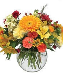 Assorted mixed seasonal cut flowers designed in a natural like setting in a glass bubble bowl.