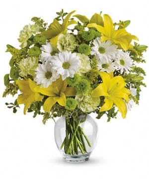 A happy bouquet of yellow lilies, green carnations and other sunny favorites beautifully arranged in a classic ginger jar