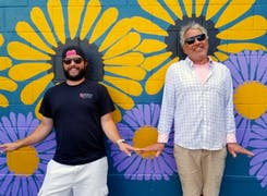 A pair of Boesen's owners clowning around near a floral-themed mural
